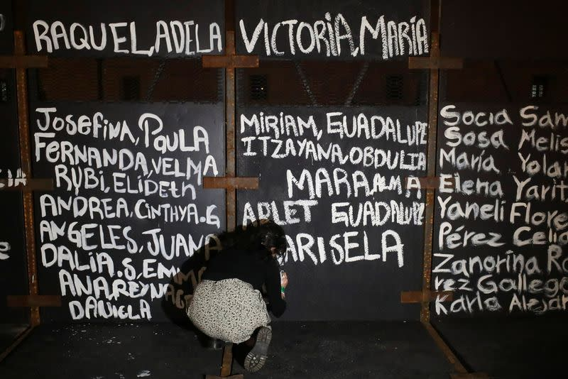 A woman paints the names of victims of femicide in Mexico on fences placed outside the National Palace ahead of a Women's Day protest, in Mexico City
