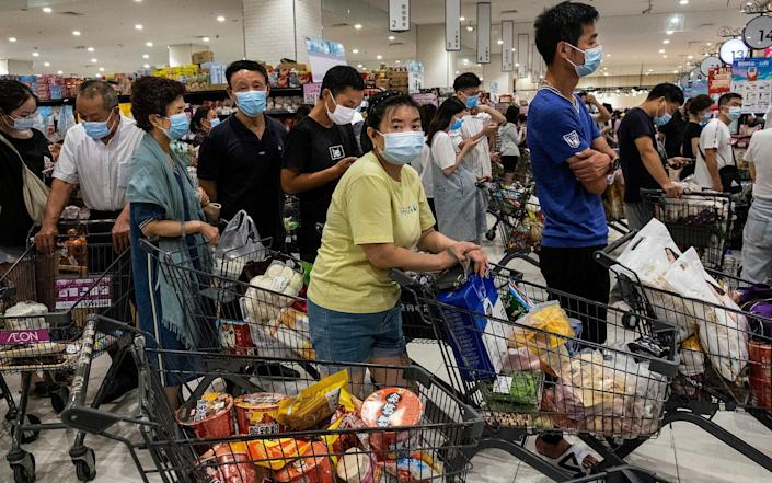 Masked shoppers line up to pay for goods as it was announced Wuhan would be testing all 11million of its population after a Covid outbreak - Getty