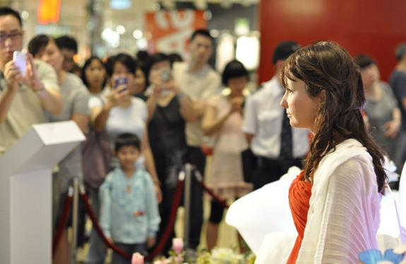 A Geminoid robot made by the Hiroshi Ishiguro Laboratory sits in front of a crowd in Hong Kong.