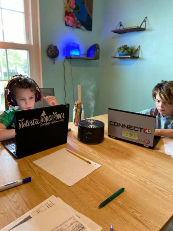 two kids working on laptops
