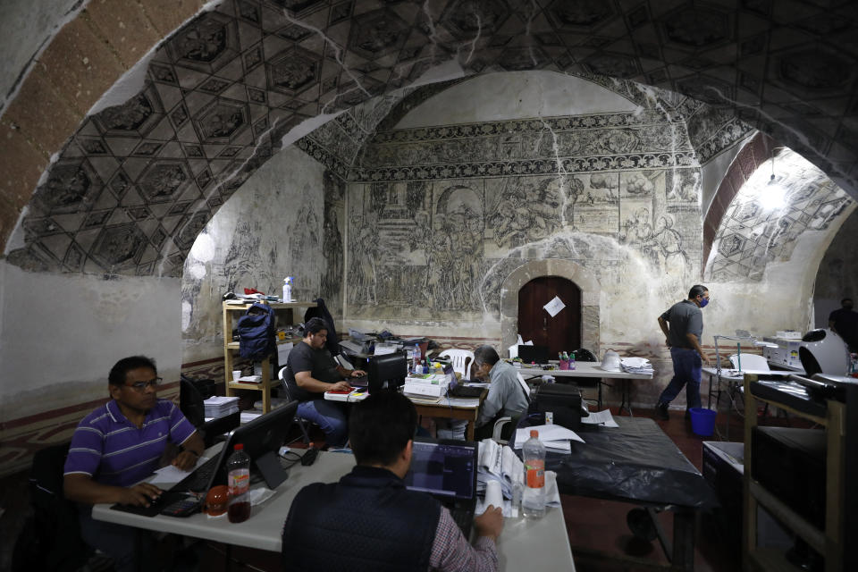 Employees of the construction company entrusted with the restoration of the former San Juan Bautista Convent work at desks set up beneath painted vaults in a building adjacent to the church that was damaged in a 2017 earthquake, in Tlayacapan, Morelos state, Mexico, Tuesday, Oct. 13, 2020. The convent was started in 1554, soon after the conquest. (AP Photo/Rebecca Blackwell)