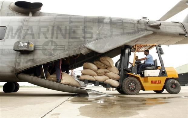 World Food Programme (WFP) workers load bags of flour for flood victim relief onto a U.S. Marine CH-53E helicopter while waiting for weather to clear at an airbase in Pakistan's northwest Khyber-Pakhtunkhwa Province August 16, 2010.