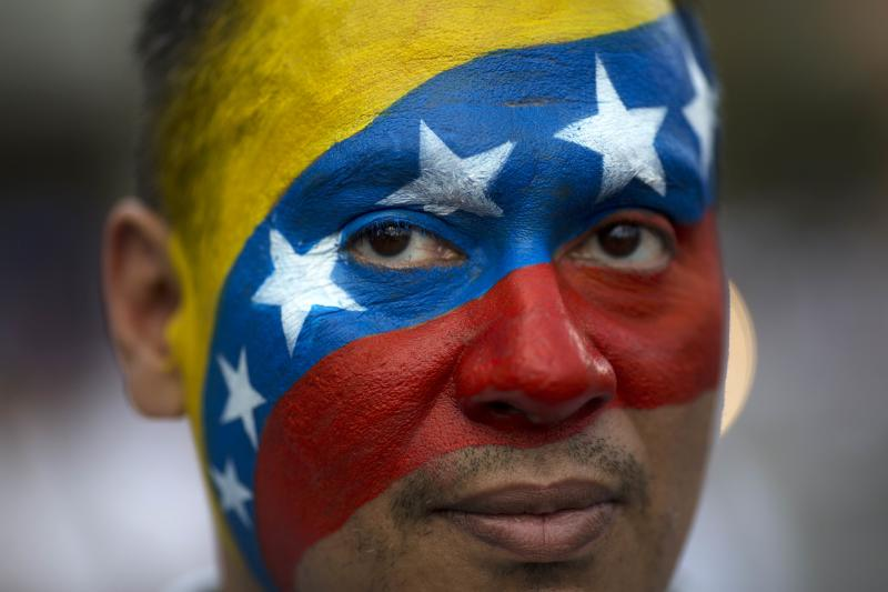 David Aranguren, his face painted with a representation of Venezuela's national flag, poses for a photo during an anti-government demonstration in Caracas, Venezuela, Saturday, Feb. 22, 2014. Supporters and opponents of the government of President Nicolas Maduro are holding competing rallies in the bitterly divided country. (AP Photo/Rodrigo Abd)