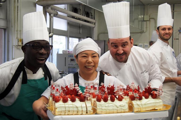 French chef Christoph Paucod (2nd R) and members of his French chef team 'Caravan bon appetit' with a cake they have prepared at an elementary school in Koriyama, on December 9, 2013