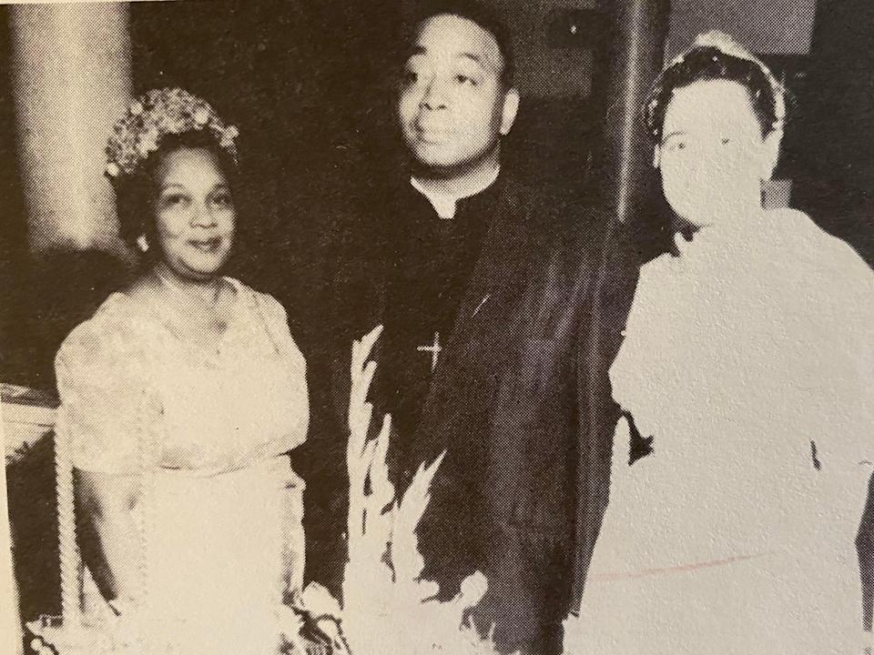 a woman wearing church clothes and a fancy hat poses with a reverend and another woman in white