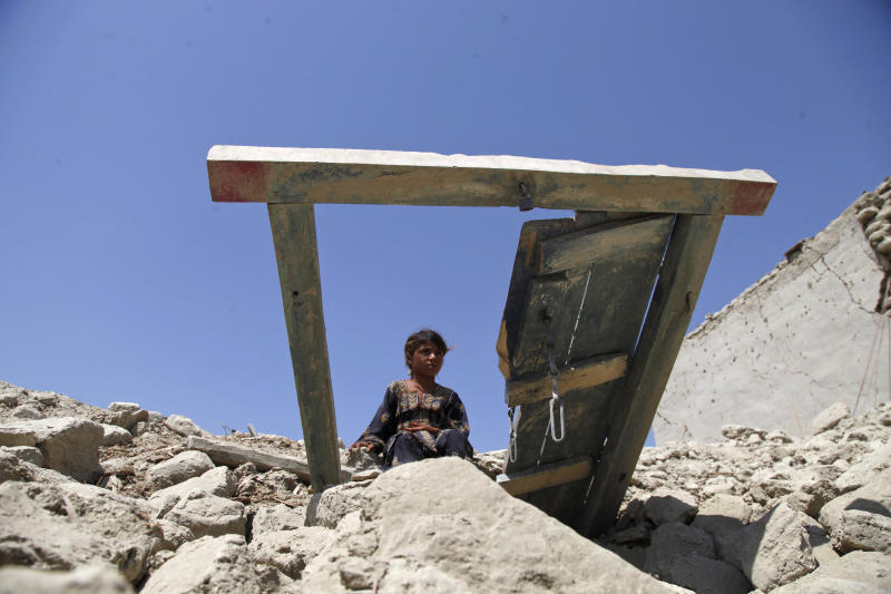 A Pakistani girl sits on the rubble of her house destroyed by Tuesday's earthquake in Labach, the remote district of Awaran in Baluchistan province, Pakistan, Thursday, Sept. 26, 2013. Two days after the tremor struck, rescuers were still struggling to help survivors. The death toll from the quake reached in hundreds on Thursday, with more than 500 people injured. (AP Photo/Shakil Adil)