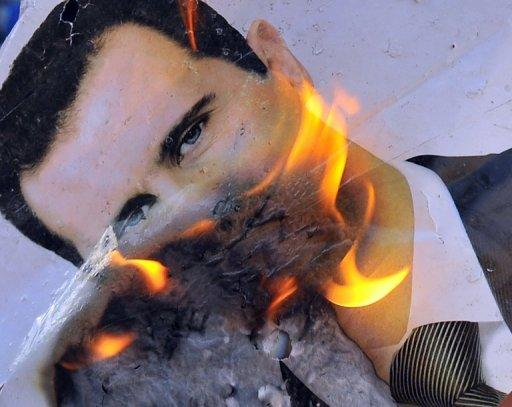 A portrait of Syria President Bashar al-Assad is set alight on July 23 during clashes near Aleppo