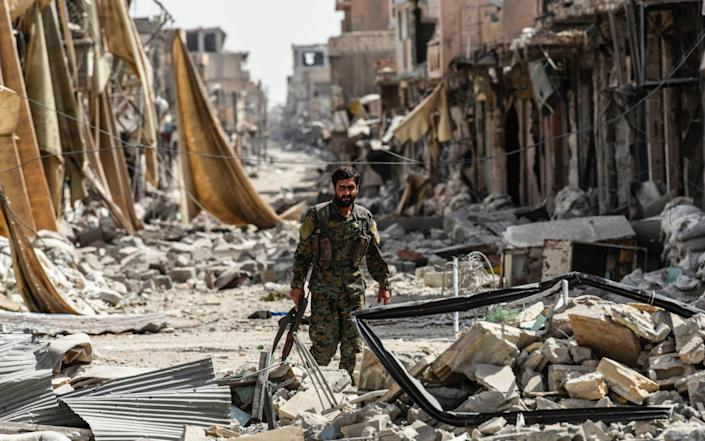 A member of the Syrian Democratic Forces (SDF) walks through the debris in the old city centre on the eastern frontline of Raqa  - AFP