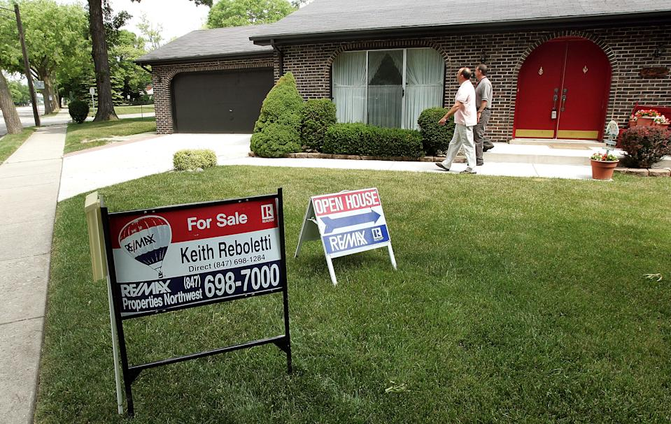 PARK RIDGE, IL - JUNE 13: ReMax realtor Keith Reboletti, right, walks with Coldwell Banker realtor Joseph Zei outside of a home for sale during a realtor's open house showing he was holding June 13, 2005 in Park Ridge, Illinois. Unusually low mortgage rates of late have been a boom to the housing market and some real estate companies. (Photo by Tim Boyle/Getty Images)