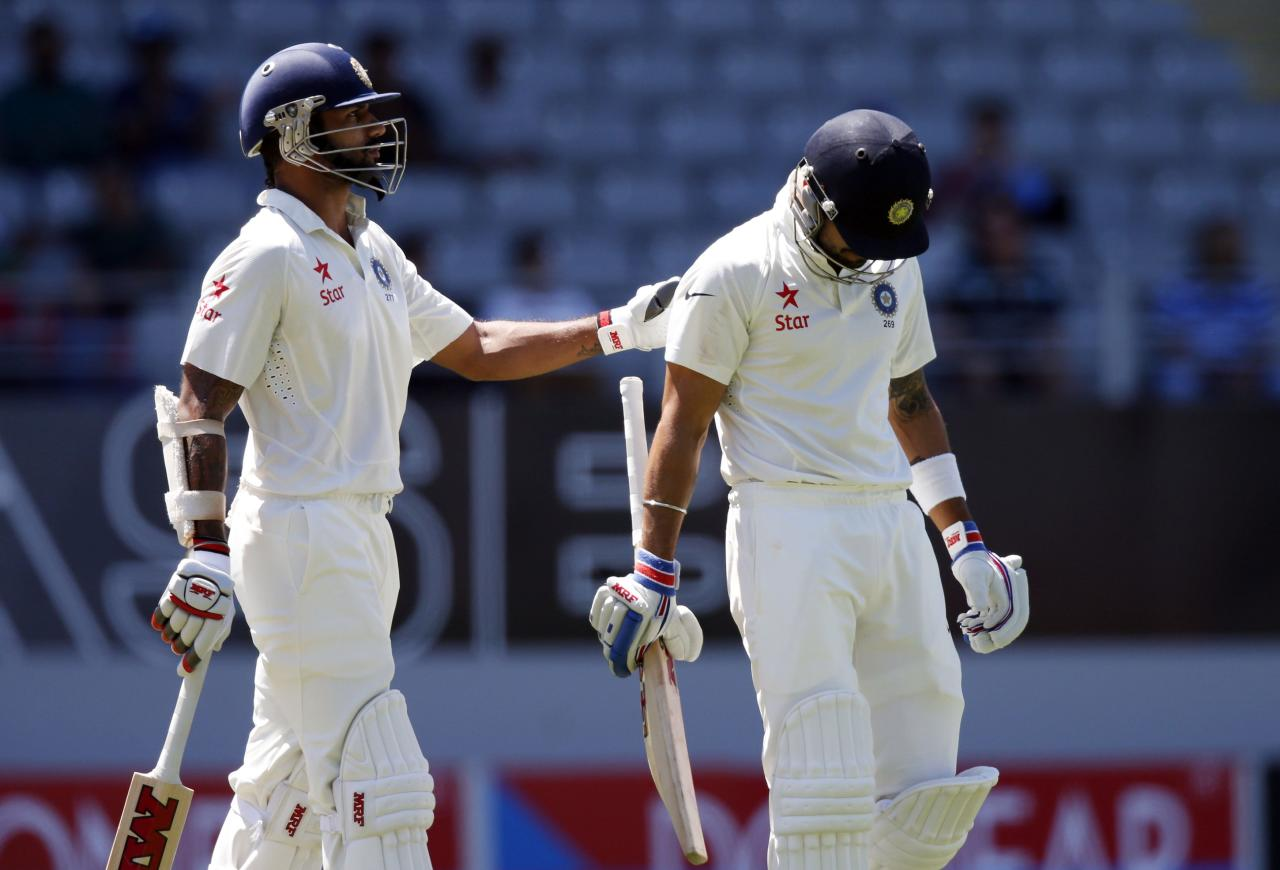 India's Shikhar Dhawan (L) consoles Virat Kohli after he was dismissed during his second innings on day four of the first international test cricket match against New Zealand at Eden Park in Auckland, February 9, 2014. REUTERS/Nigel Marple (NEW ZEALAND - Tags: SPORT CRICKET)