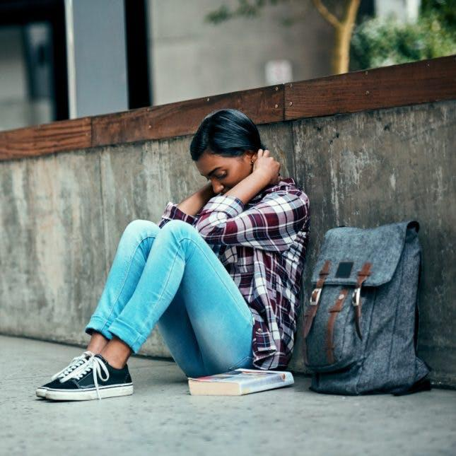 A stressed student sits along a wall