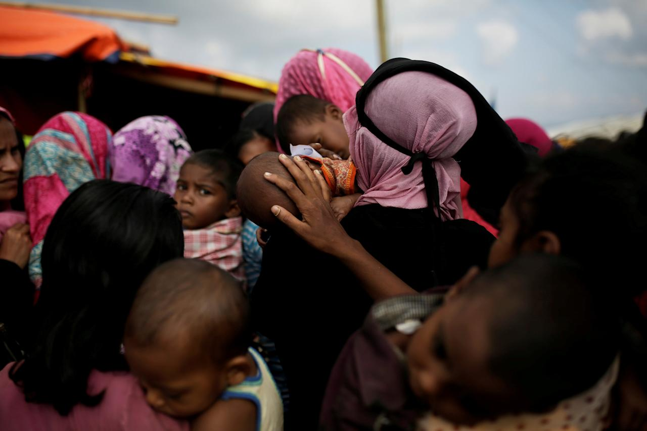 A woman calms a baby as Rohingya refugees line up for a food supply distribution at the Kutupalong refugee camp near Cox's Bazar, Bangladesh December 12, 2017. REUTERS/Alkis Konstantinidis     TPX IMAGES OF THE DAY