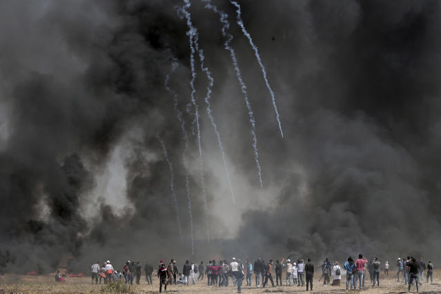 <p>Palestinian protesters gather in front of burned tires while Israeli soldiers fire teargas during clashes with Israeli troops along Gaza's border with Israel, east of Khan Younis, Gaza Strip, Friday, April 6, 2018. (Photo: Adel Hana/AP) </p>