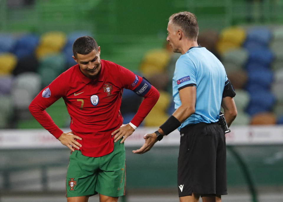 FILE - In this Wednesday, Oct. 7, 2020 file photo Portugal's Cristiano Ronaldo, left, reacts as he speaks with referee Paolo Valeri during the international friendly soccer match between Portugal and Spain at the Jose Alvalade stadium in Lisbon. The Portuguese soccer federation says Cristiano Ronaldo has tested positive for the coronavirus. The federation says Ronaldo is doing well and has no symptoms. He has been dropped from the country's Nations League match against Sweden on Wednesday. (AP Photo/Armando Franca, File)