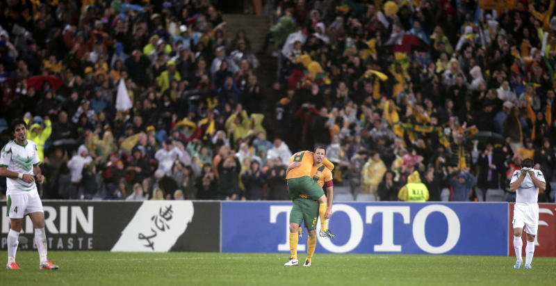 Australia's captain Lucas Neill, center right, carries teammate Luke Wilkshire after their victory over Iraq in their World Cup soccer Asian qualifying match at the Sydney Olympic Stadium in Sydney, Australia, Tuesday, June 18, 2013. Australia won the match 1-0 and qualify for the 2014 World Cup in Brazil. (AP Photo/Rick Rycroft)