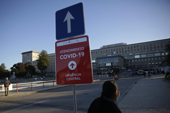 FILE - In this Jan. 18, 2021, file photo, a sign shows the way to the COVID-19 emergency ward at the Santa Maria hospital in Lisbon. In its fight against COVID-19, Portugal lifted restrictions on gatherings and movements for four days over Christmas so that people could spend the festive season with family and friends. Soon after the holiday, the pandemic quickly got out of hand. (AP Photo/Armando Franca)