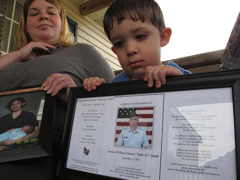 FILE - In this March 18, 2013, file photo, Shane Mercer points to a photo of his father, Airman Will Small, as his mother Alecia Mercer looks on at their home in Kinston, N.C. Small, whose organs were donated to four patients after he died, had at least two untreated raccoon bites several months before he became sick, and tests confirm his rabies-infected kidney led to a recipient's death, according to a report published Tuesday, July 23, 2013 in the Journal of the American Medical Association. (AP Photo/Allen Breed, File)