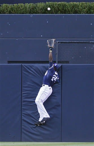 San Diego Padres center fielder Cameron Maybin goes up high at the wall to rob San Francisco Giants' Xavier Nady of a home run during the first inning of a baseball game Saturday, Sept. 29, 2012 in San Diego. (AP Photo/Lenny Ignelzi)