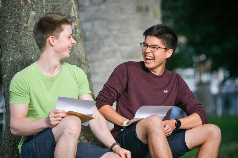 Benjamin Sheridan, 19, (left) and John Brown, 18, laugh as they share their A Level results at St Mary Redcliffe and Temple School, Bristol. (Photo by Ben Birchall/PA Images via Getty Images)