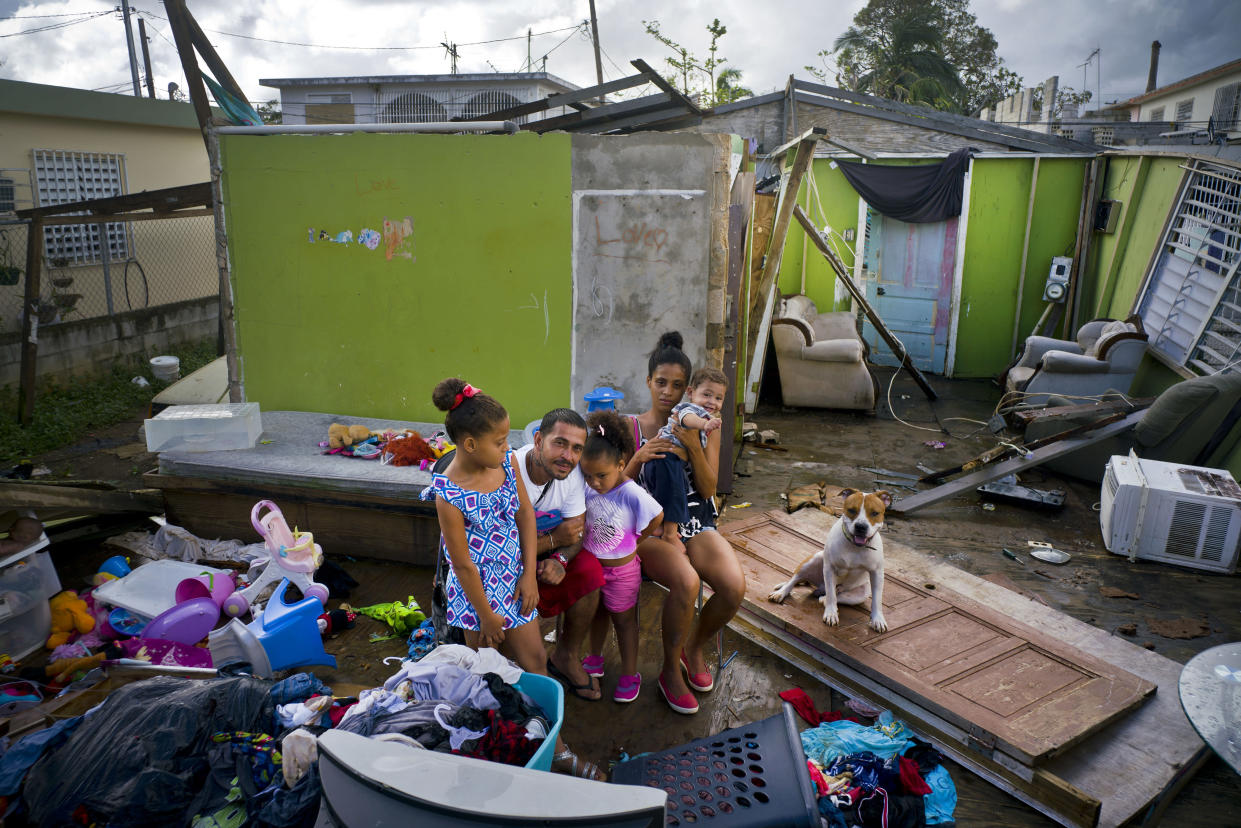In this photo from October, Arden Dragoni, second from left, poses with his wife, Sindy, their three children and dog Max, surrounded by what remains of their home destroyed by Hurricane Maria in Toa Baja, Puerto Rico. (Photo: Ramon Espinosa/AP)