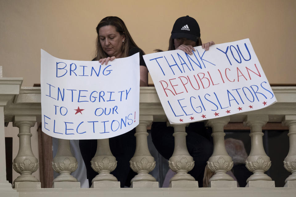Protesters in favor of changes in Georgia's voting laws hold signs inside the State Capitol in Atlanta, Ga., as the Legislature meets Monday, March 8, 2021, in Atlanta. (AP Photo/Ben Gray)