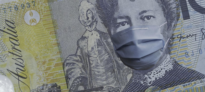 COVID-19 coronavirus in Australia, australian dollar money bill with face mask. COVID global stock market affection. World economy hit by corona virus outbreak. Financial crisis and coronavirus pandemic concept
