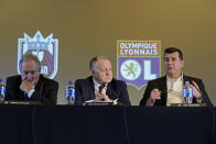 Jean-Michel Aulas, center, owner and president of the French soccer team Olympique Lyonnais, and OL Groupe's Gerard Houllier, left, listen as Bill Predmore, right, former owner of the National Women's Soccer League Reign FC team, speaks Thursday, Dec. 19, 2019, at a news conference in Tacoma, Wash. OL Groupe, the parent company of Olympique Lyonnais, is buying Reign FC, of the in a transaction expected to close in January 2020. Reign FC will continue to play its home games at Cheney Stadium, the venue it shares with the Triple-A minor league baseball team the Tacoma Rainiers. (AP Photo/Ted S. Warren)