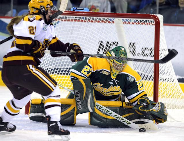 Clarkson goaltender Erica Howe, right, makes a save against Minnesota's Dani Cameranesi during the second period of an NCAA college hockey game in the finals of the women's Frozen Four in Hamden, Conn., Sunday, March 23, 2014. (AP Photo/Fred Beckham)