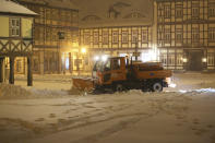 A clearing vehicle clears the snow in the city centre in the early hours of the morning on Sunday, Feb. 7, 2021 in Wernigerode, Germany. Deep Tristan has caused huge amounts of snow in the Harz mountains, like here in Wernigerode. (Matthias Bein/dpa via AP)