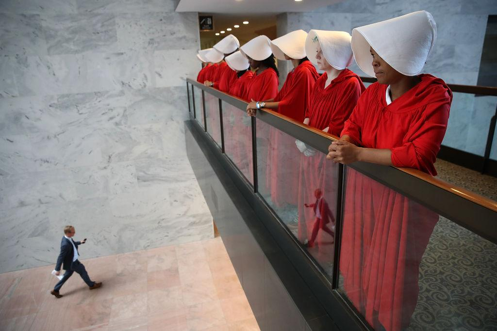 <p>WASHINGTON, DC – SEPTEMBER 04: Protesters dressed in The Handmaid's Tale costume, protest outside the hearing room where Supreme Court nominee Judge Brett Kavanaugh will testify before the Senate Judiciary Committee during his Supreme Court confirmation hearing in the Hart Senate Office Building on Capitol Hill September 4, 2018 in Washington, DC. Kavanaugh was nominated by President Donald Trump to fill the vacancy on the court left by retiring Associate Justice Anthony Kennedy. (Photo by Win McNamee/Getty Images) </p>