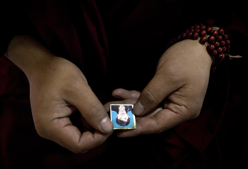 In this Wednesday, Oct. 16, 2013 photo, a Tibetan, cousin of Sangay Gyatso holds a photo of Sangay Gyatso, who fatally set himself ablaze in Gannan Tibetan Autonomous Prefecture, China. By the official account, Sangay Gyatso was an incorrigible thief and womanizer who was goaded into setting himself on fire in an elaborate and cruel scheme to fan up ethnic hatred. But one year after the 27-year-old father of two fatally set himself ablaze near a white stupa near his Gannan village, his cousin denied the government's account. (AP Photo/Andy Wong)