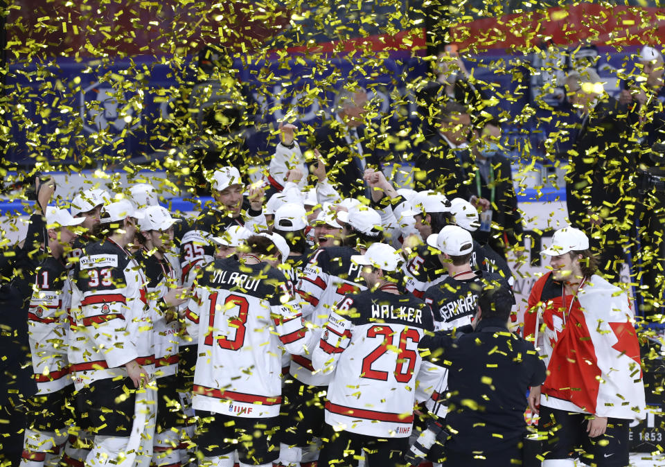 Canada's team players celebrate with the trophy after winning the Ice Hockey World Championship final match between Finland and Canada at the Arena in Riga, Latvia, Sunday, June 6, 2021. (AP Photo/Sergei Grits)