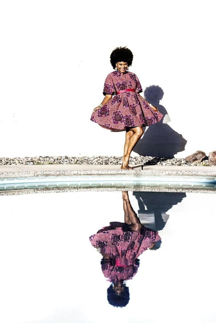 Tabitha Brown poses over a reflection of herself in a body of water outdoors.