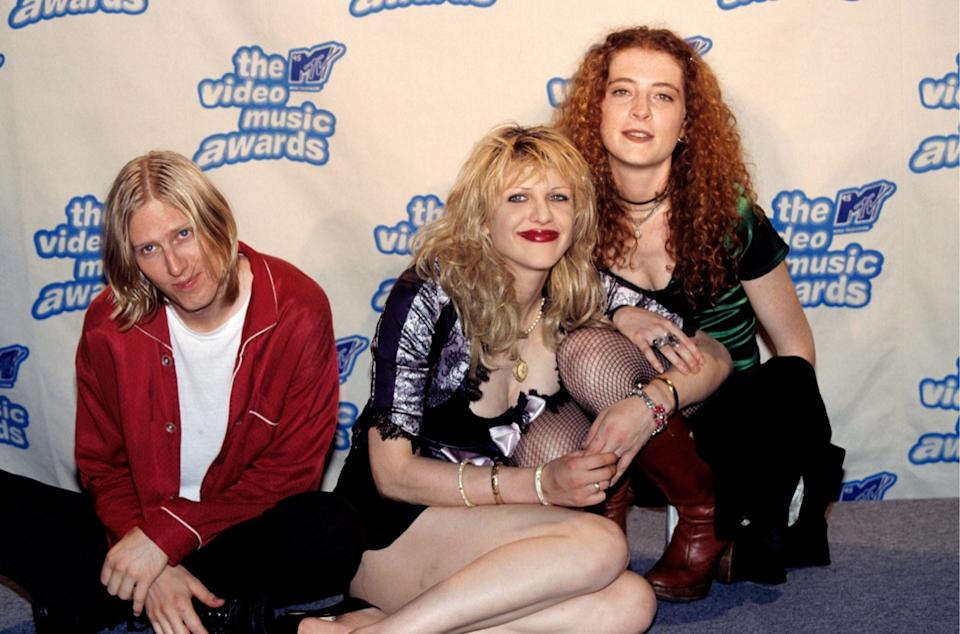 the members of the band hole, including courtney love, sit on the red carpet at the 1995 mtv video music awards, wearing a 90s baby doll dress