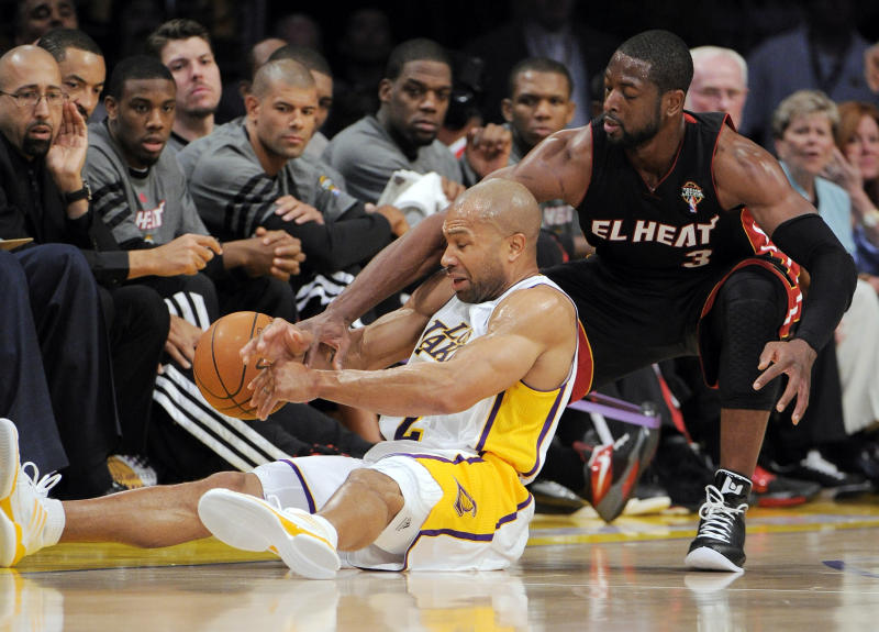 Los Angeles Lakers guard Derek Fisher, left, and Miami Heat guard Dwyane Wade battle for a loose ball during the first half of their NBA basketball game, Sunday, March 4, 2012, in Los Angeles. (AP Photo/Mark J. Terrill)