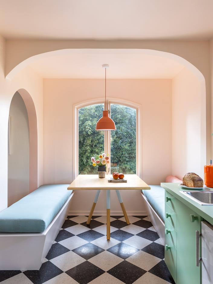 """""""This is where you'll find one of the most calming and magical views in the whole house,"""" Laurel says. The banquette cushions are covered in Sunbrella's Canvas Spa and Muuto's Unfold pendant hangs above a found table."""