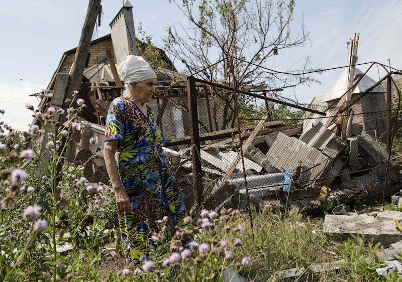 A woman walks past her damaged house, which according to locals was hit by recent shelling, the village of Sakhanka in Donetsk region, Ukraine