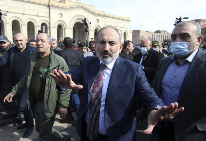 Armenian Prime Minister Nikol Pashinyan greets his supporters as he arrives at the main square in Yerevan, Armenia, Thursday, Feb. 25, 2021. Armenia's prime minister has spoken of an attempted military coup after facing the military's General Staff demand to step down. The developments come after months of protests sparked by the nation's defeat in the Nagorno-Karabakh conflict with Azerbaijan. (Stepan Poghosyan/PHOTOLURE via AP)