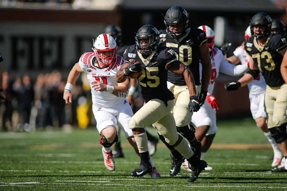 Wake Forest running back Kenneth Walker III carries the ball while N.C. State's Payton Wilson pursues in last season's game.