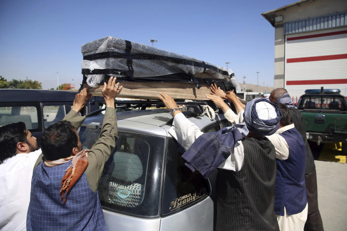 Families receive bodies of their relatives who drowned after their boat sank in Turkey's Lake Van, at the Hamid Karzai International Airport in Kabul, Afghanistan, Wednesday, July 22, 2020. The boat sank last month while ferrying dozens of migrants across a lake in eastern Turkey. (AP Photo/Rahmat Gul)