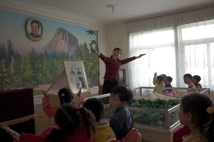 In this photo taken on Friday, April 27, 2012, a North Korean teacher gestures to her class while teaching the history of their former leader Kim Jong Il at the Kaeson Kindergarten in Pyongyang, North Korea. For North Koreans, the systematic indoctrination of anti-Americanism starts as early as kindergarten and is as much a part of the curriculum as learning to count. (AP Photo/Vincent Yu)