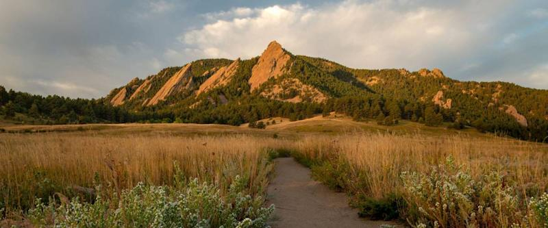A hiking path leads to the Flatiron Mountains and adventure in Boulder Colorado's Chautauqua Park.