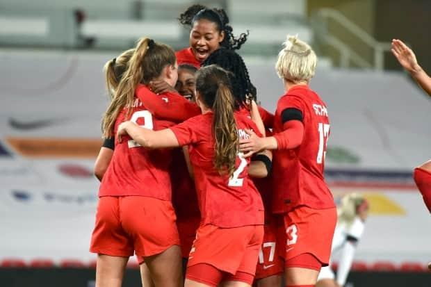 Canada players celebrate a goal against England during a friendly match on Tuesday in Stoke-on-Trent, England. (Rui Vieira/The Associated Press - image credit)