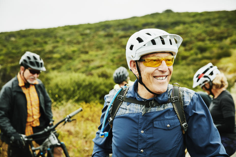 Portrait of smiling senior man hanging out with friends before early morning mountain bike ride