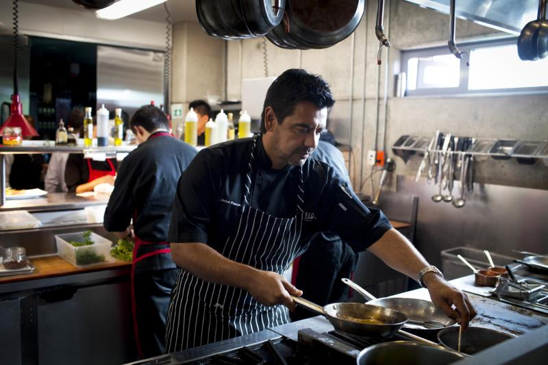 In this Sept. 27, 2012 photo, Chef Javier Plascencia cooks in the kitchen at Mission 19 restaurant in Tijuana, Mexico. Plascencia is part of a group of chefs working to create a unique cuisine largely based on fresh seafood caught in the seas flanking Baja and the produce from its fertile valley. The new culinary craze, known as Baja Med, is a fusion of Mexican food with influences from the Mediterranean and Asia. (AP Photo/Alex Cossio)