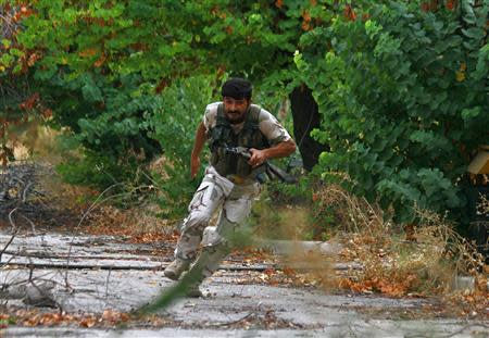 A Free Syrian Army fighter runs for cover from snipers loyal to Syria's President Bashar al-Assad in the Al-Sakhour neighborhood of Aleppo