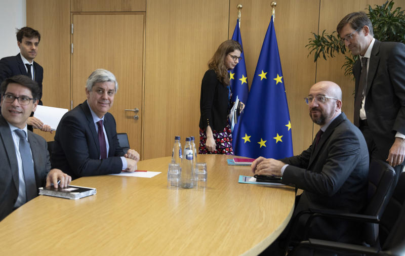 "FILE - In this Tuesday, Feb. 18, 2020 file photo Eurogroup President and Portugal's Finance Minister Mario Centeno, third left, meets with European Council President Charles Michel, second right, at the Europa building in Brussels. Governments from the 19 countries that use the euro overcame sharp differences to agree Thursday on measures that could provide more than a half-trillion euros ($550 billion) for companies, workers and health systems to cushion the economic impact of the virus outbreak. Mario Centeno, who heads the finance ministers' group from euro countries, called the package of measures agreed upon ""totally unprecedented... Tonight Europe has shown it can deliver when the will is there."" (AP Photo/Virginia Mayo, Pool, File)"
