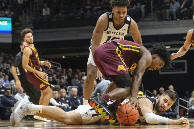 Butler forward Sean McDermott, on floor, watches as Minnesota guard Marcus Carr gets to a loose ball in the second half of an NCAA college basketball game in Indianapolis, Tuesday, Nov. 12, 2019. Butler won 64-56. (AP Photo/AJ Mast)