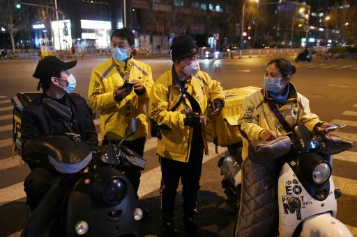 People working in food delivery wear facemasks while outside a restaurant in Beijing amid concerns over the spread of COVID-19