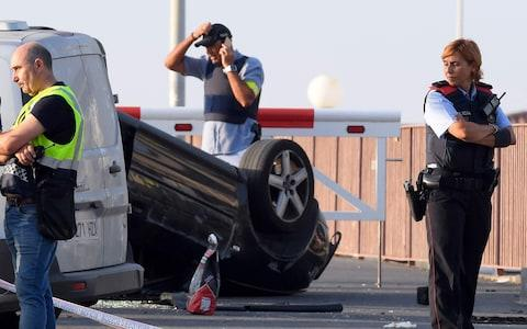 A policeman stands by a car involved in a terrorist attack in Cambrils - Credit: LLUIS GENE/AFP